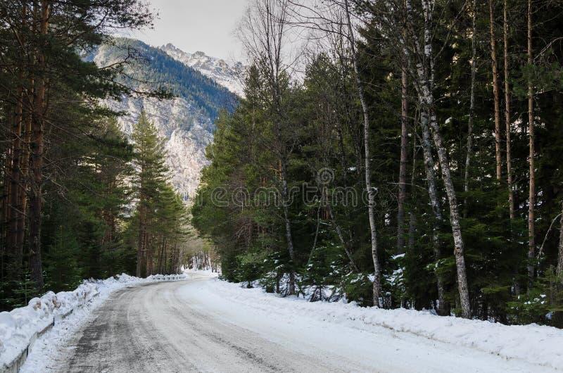 Una vista de un camino de la montaña del invierno cubierto con nieve y la arena en una carretera de asfalto del bosque del pino d foto de archivo libre de regalías