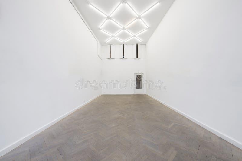 Una vista de un interior pintado blanco de un cuarto vacío o de una galería de arte con una iluminación del tragaluz y pisos conc imagen de archivo libre de regalías