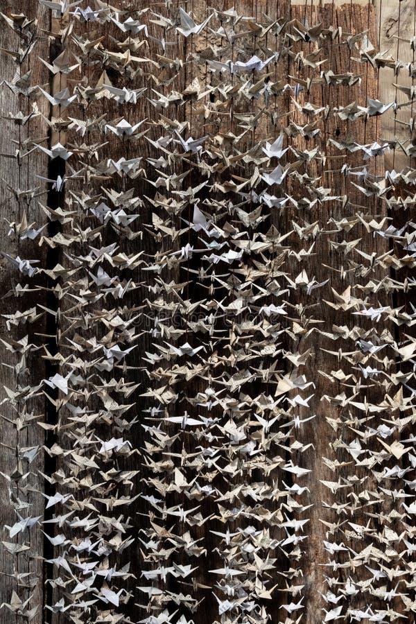 Una vista del dettaglio di una scultura di carta di 1000 gru contro vecchio fondo di legno, origami ha piegato la carta fotografia stock