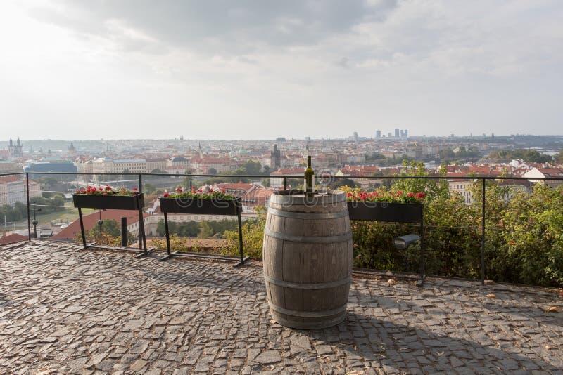 Una vista del horizonte de Praga de la montaña, de un barril viejo con la botella de vino dulce y del vidrio, República Checa imagen de archivo libre de regalías