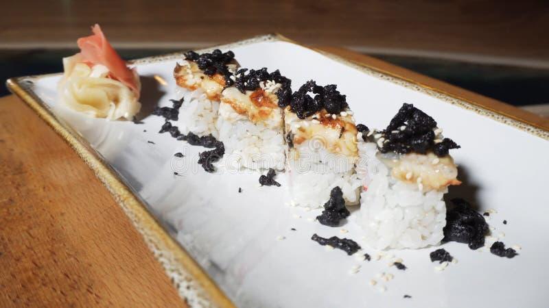 Una vista del primo piano di 4 rotoli europei deliziosi con l'anguilla, il wasabi e lo zenzero mettere su un piatto girante bianc fotografie stock