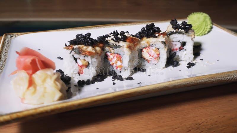 Una vista del primo piano di 4 rotoli europei deliziosi con l'anguilla, il wasabi e lo zenzero mettere su un piatto girante bianc fotografia stock