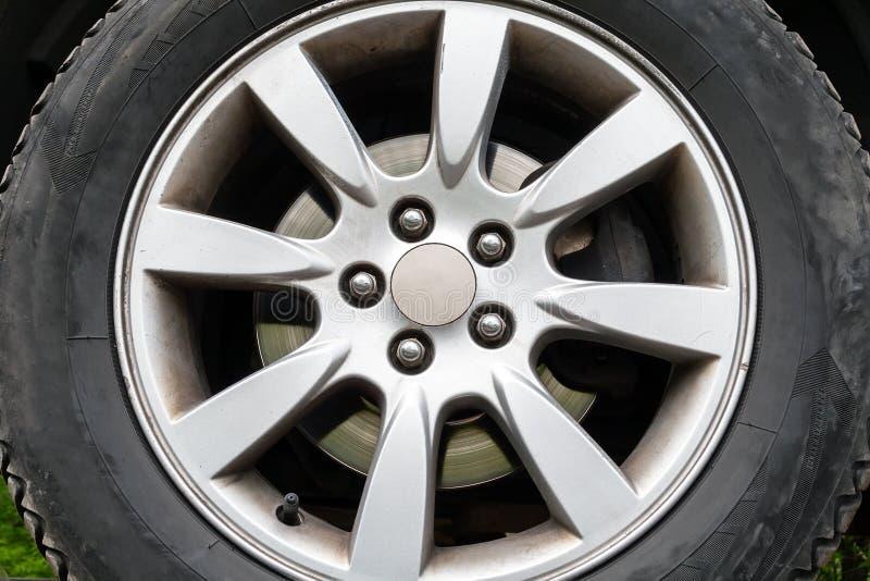 Una vista del primo piano di una ruota di automobile con le gomme di inverno, il disco d'argento del freno e un orlo del cinque-d fotografia stock