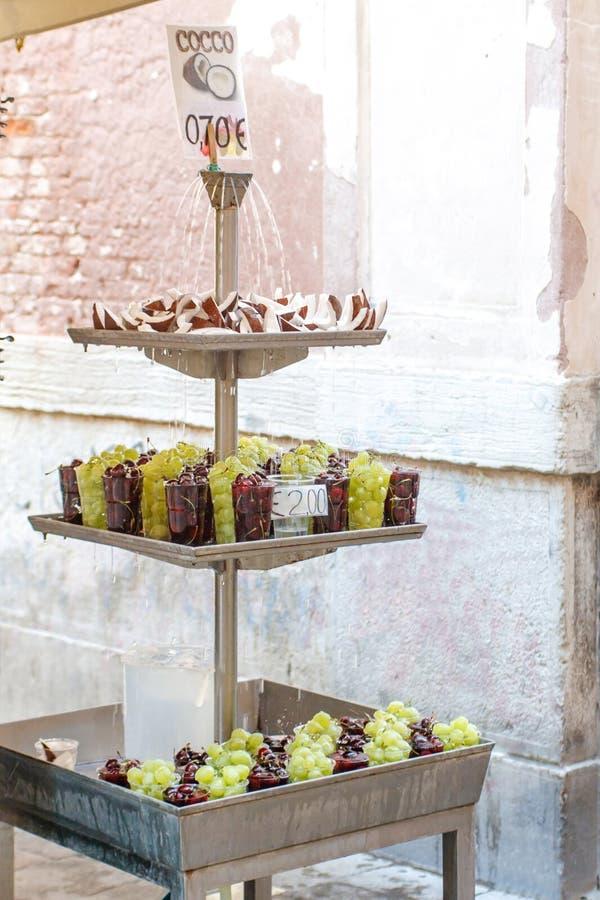 Una vista del ritratto della fontana con le gocce di acqua che cadono sulle fette della noce di cocco e sulle ciliege rosse fresc immagine stock libera da diritti