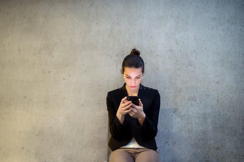 Una vista delantera de la mujer de negocios joven con el smartphone que se sienta contra el muro de cemento en oficina imagen de archivo