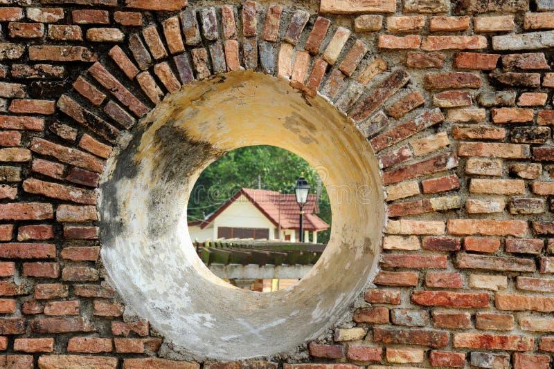 Una vista della casa attraverso una feritoia del cannone nell'isola di Pangkor forte olandese fotografie stock