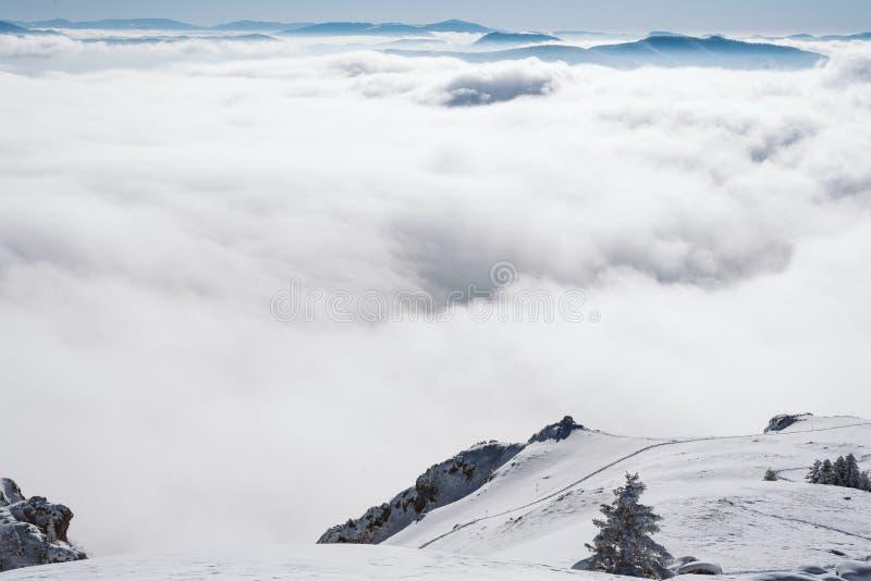 Una vista delle scogliere dell'alta montagna sulla valle coperta di nebbia immagini stock libere da diritti