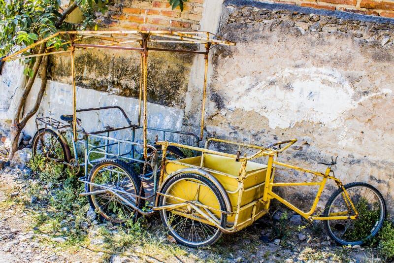 Una vista di due biciclette abbandonate una del carico blu e dell'altro giallo fotografia stock