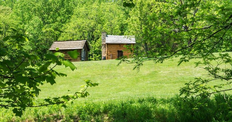 Una vista di un affumicatoio e di una cabina di ceppo fotografie stock