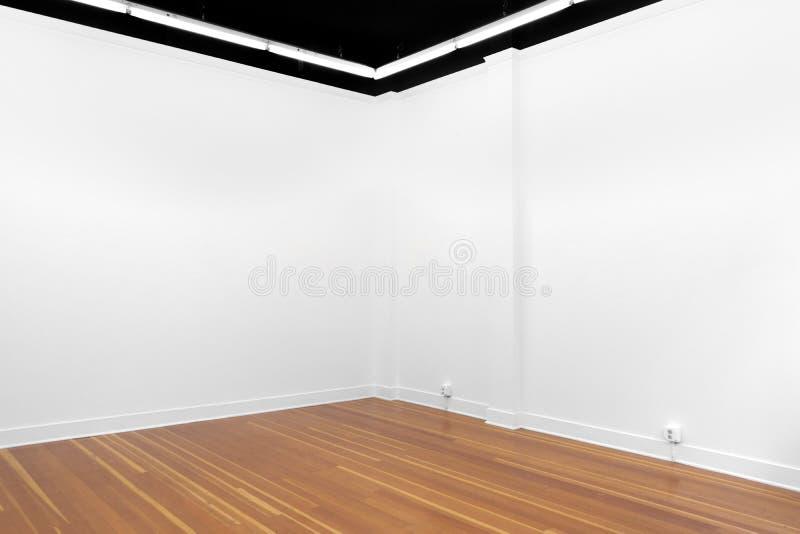 Una vista di un bianco ha dipinto l'interno di una stanza vuota o una galleria di arte con un'illuminazione fluorescente ed i pav fotografia stock