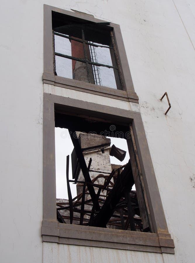 una vista di vecchio camino della fabbrica attraverso la finestra di un fabbricato industriale distrutto abbandonato con il metal fotografia stock