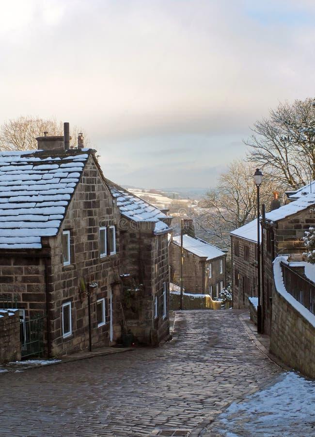 Una vista esc?nica de la calle principal en el pueblo del heptonstall en West Yorkshire con la nieve que cubre las casas de piedr imagen de archivo