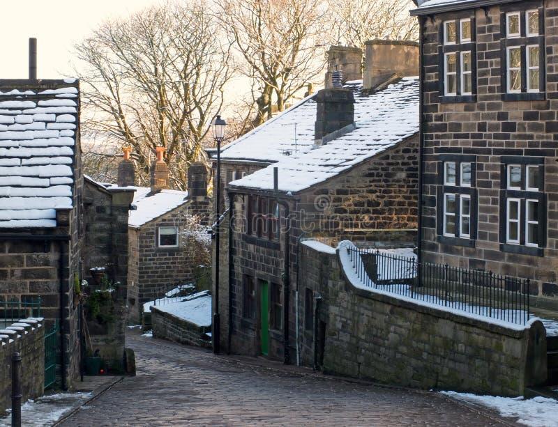 Una vista esc?nica de la calle principal en el pueblo del heptonstall en West Yorkshire con la nieve que cubre las casas de piedr fotografía de archivo