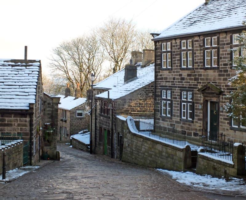 Una vista esc?nica de la calle principal en el pueblo del heptonstall en West Yorkshire con la nieve que cubre las casas de piedr imagen de archivo libre de regalías