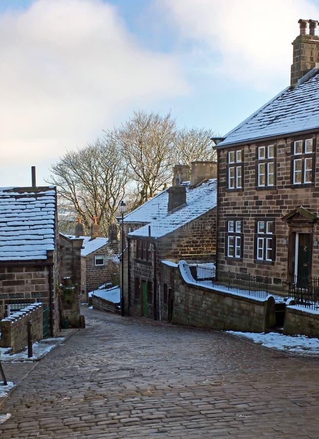Una vista esc?nica de la calle principal en el pueblo del heptonstall en West Yorkshire con la nieve que cubre las casas de piedr imágenes de archivo libres de regalías