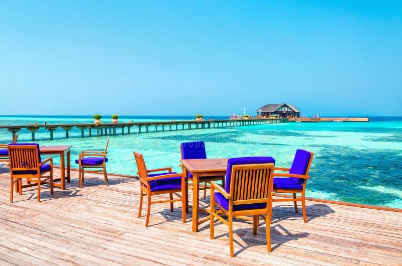 Una vista esotica di un ristorante di legno sui trampoli su un fondo di acqua azzurrata e del cielo soleggiato fotografie stock