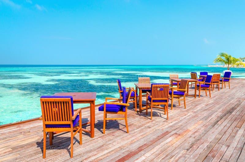 Una vista esotica di un ristorante di legno sui trampoli su un fondo di acqua azzurrata e del cielo soleggiato immagine stock libera da diritti