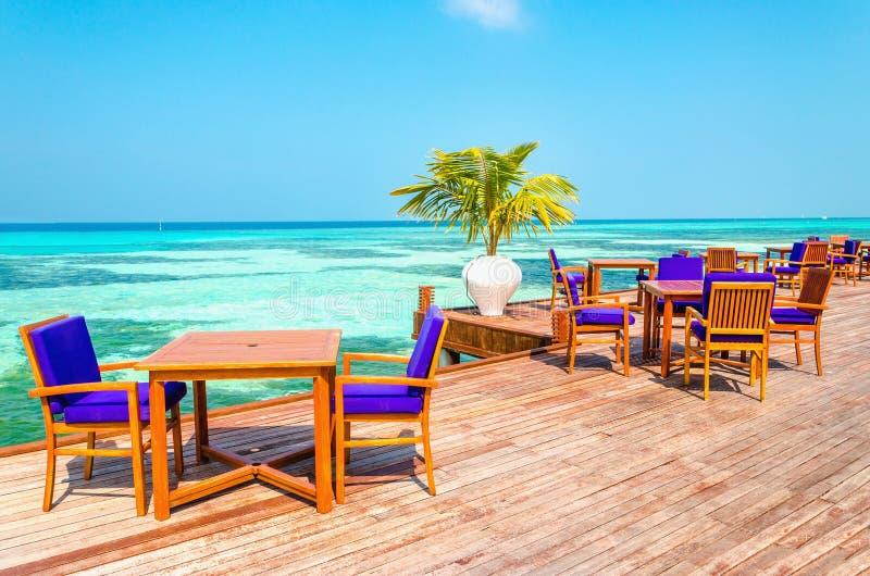 Una vista esotica di un ristorante di legno sui trampoli su un fondo di acqua azzurrata e del cielo soleggiato fotografia stock libera da diritti