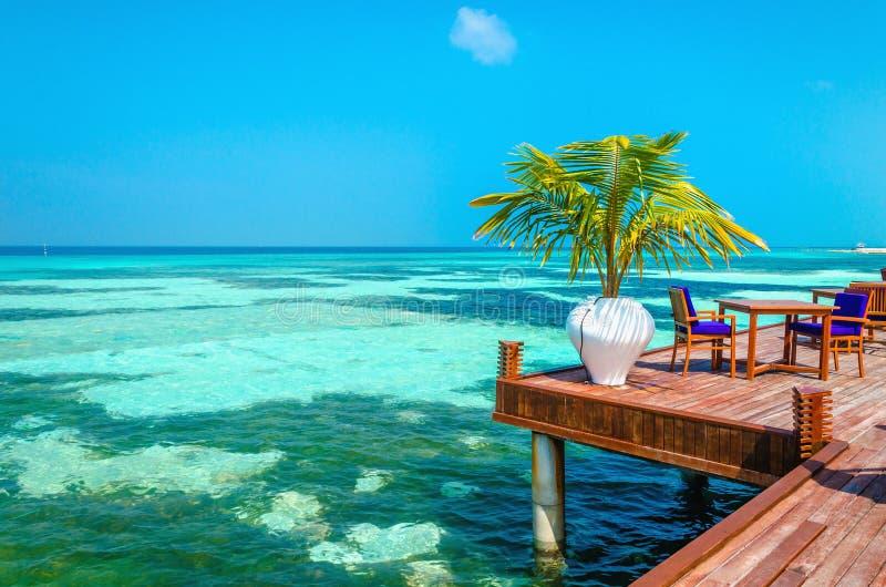 Una vista esotica di un ristorante di legno sui trampoli su un fondo di acqua e di cielo blu azzurrati fotografie stock