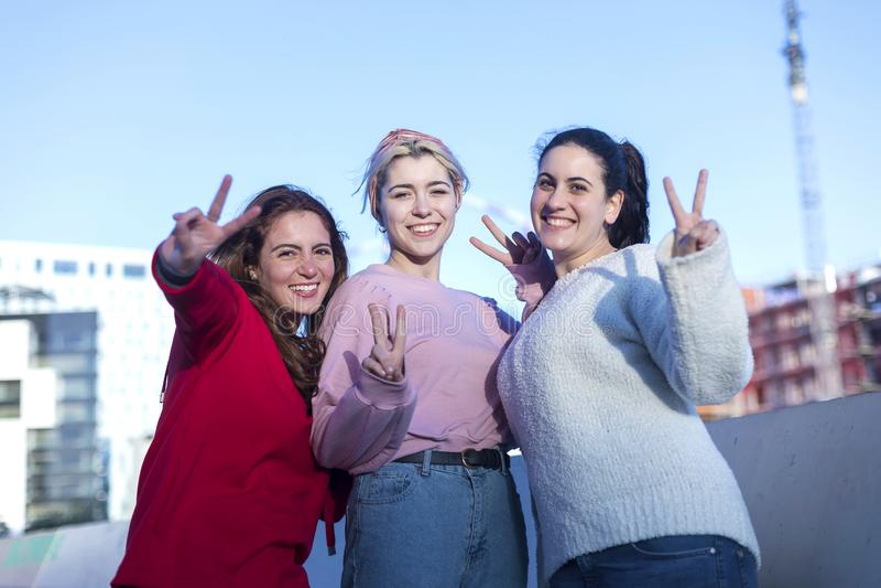 Una vista frontale di tre adolescenti che fanno un segno di pace all'aperto in un giorno soleggiato fotografia stock libera da diritti