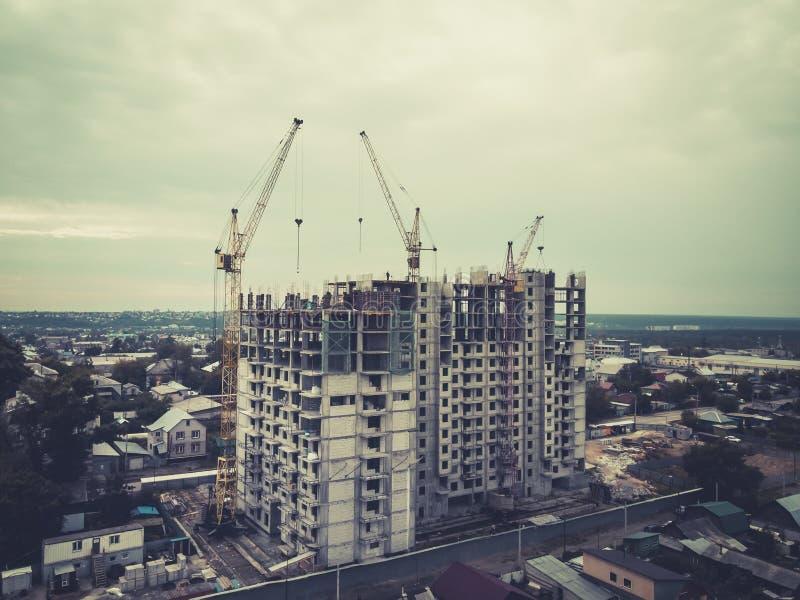 Una vista a la construcción de viviendas de varios pisos entre las cabañas Etapa inicial de la construcción de viviendas multifam foto de archivo