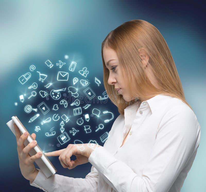 Una vista lateral de la mujer joven hermosa que hojea una cierta información en el Innternet usando la tableta Medios iconos soci foto de archivo