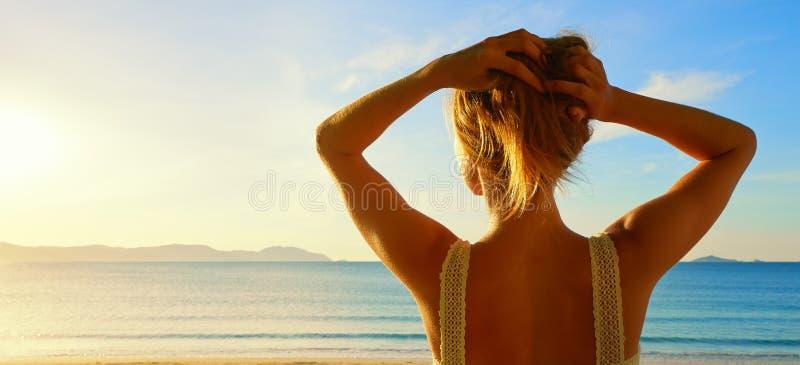 Una vista lateral trasera sobre una mujer joven maravillosa que mira al mar y fotografía de archivo
