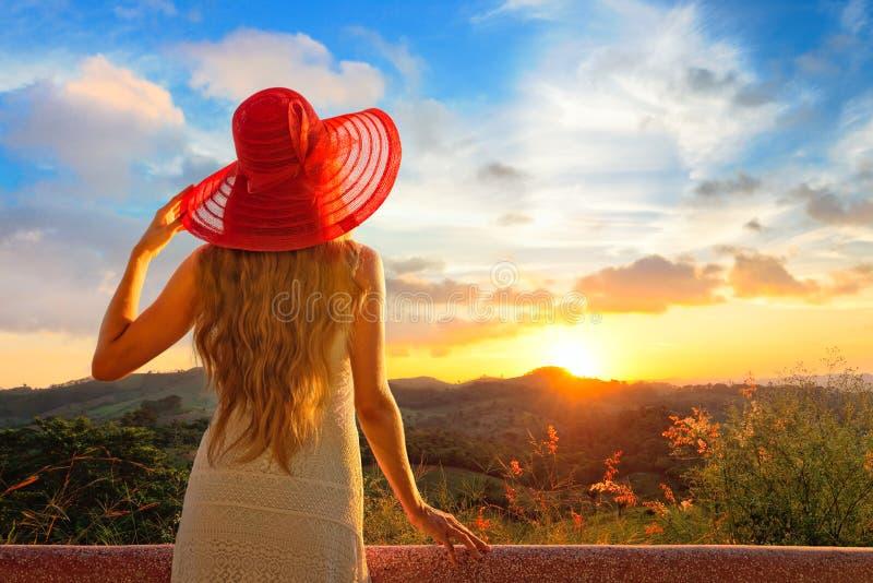Una vista lateral trasera sobre una puesta del sol de observación maravillosa de la mujer joven imagen de archivo