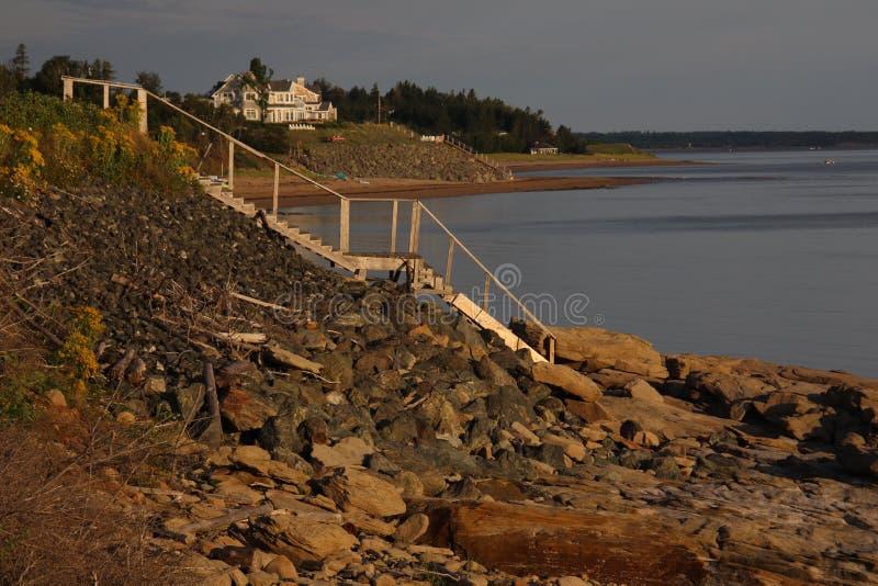 Una vista laterale di una scala di legno che conduce giù all'acqua da una collina immagine stock
