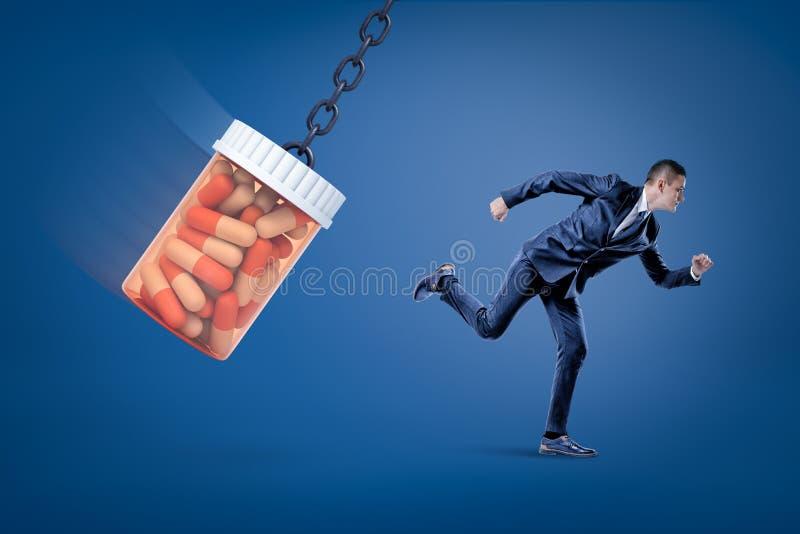 Una vista laterale di un uomo d'affari che corre dall'pillole piene enormi stona l'oscillazione su una catena su un fondo blu fotografia stock