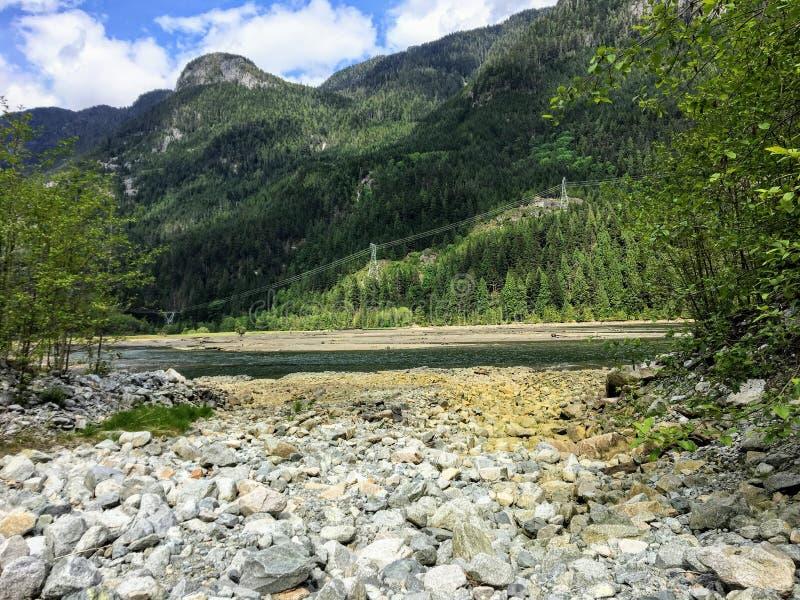 Una vista lejana de las líneas eléctricas que corren a través de un bosque en el lado de una montaña al lado de una entrada imagenes de archivo