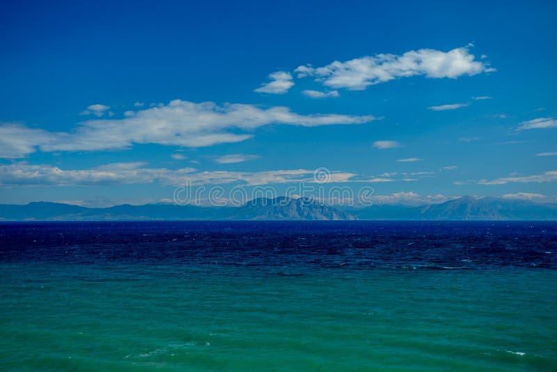 Una vista magnifica sopra il bello livello del mare blu-verde alle montagne distanti sulla costa greca fotografia stock
