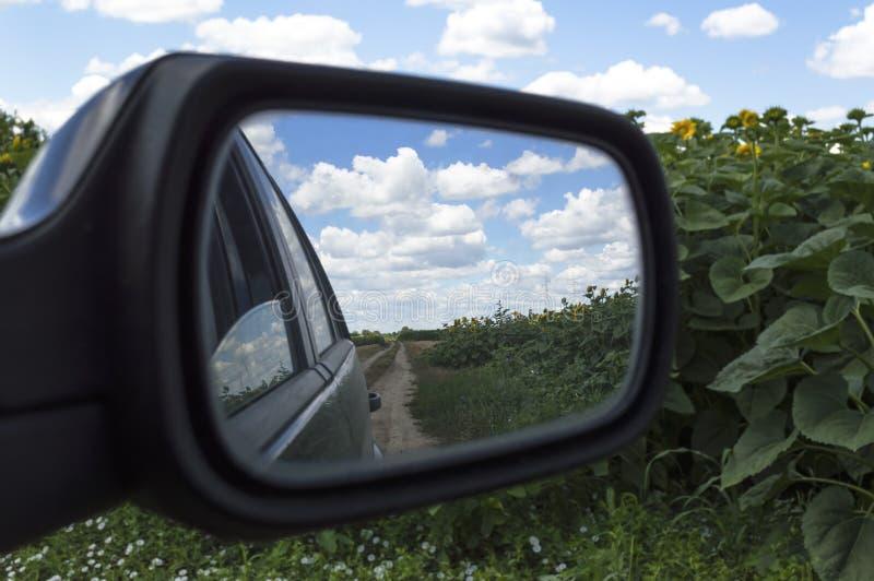 Una vista nello specchio di vista laterale Riflessione della strada campestre immagini stock