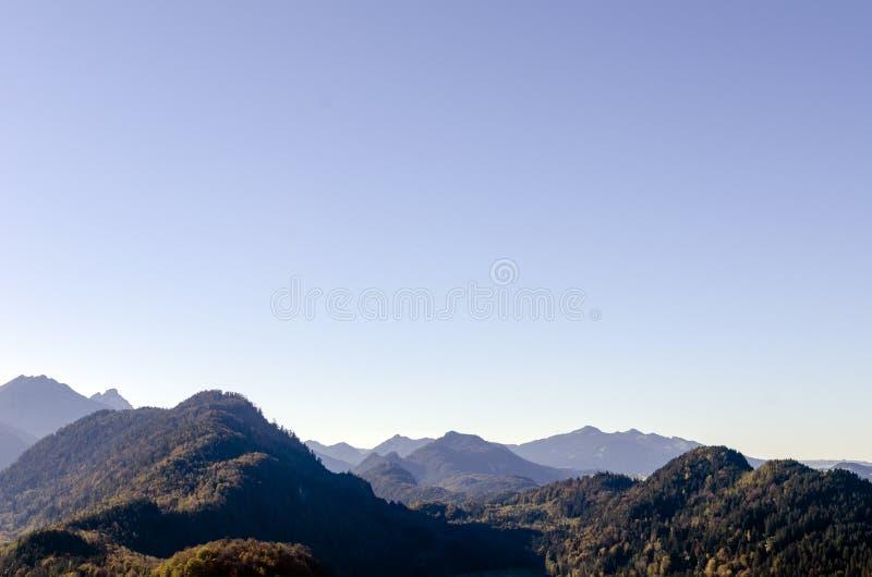 Una vista panorámica espaciosa de las montañas de las montañas cubiertas con los árboles coloridos en un día soleado de octubre c imagen de archivo libre de regalías