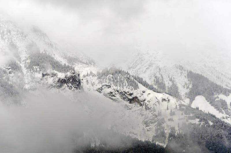 Una vista panorámica misteric de niebla de las montañas de las montañas cubiertas parcialmente con la nieve en un octubre nublado imágenes de archivo libres de regalías
