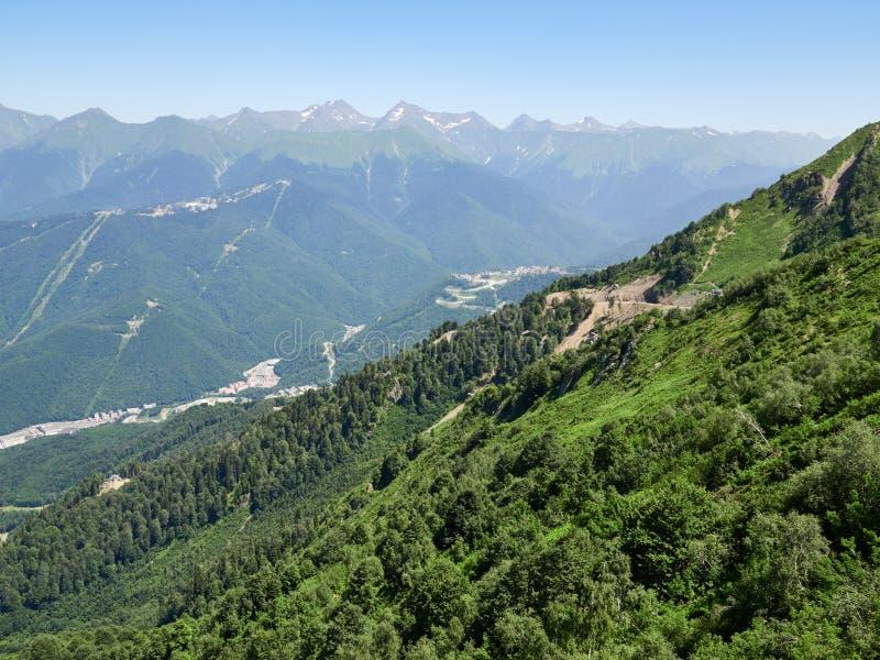 Una vista panoramica della valle con le costruzioni di appartamento, circondata dalle montagne con le cabine di funivia fotografia stock libera da diritti
