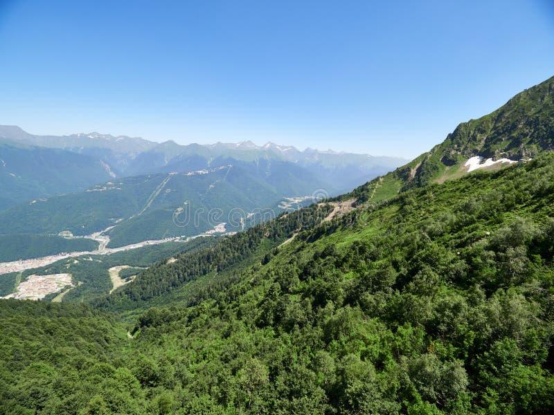 Una vista panoramica della valle con le costruzioni di appartamento, circondata dalle montagne con le cabine di funivia fotografie stock libere da diritti
