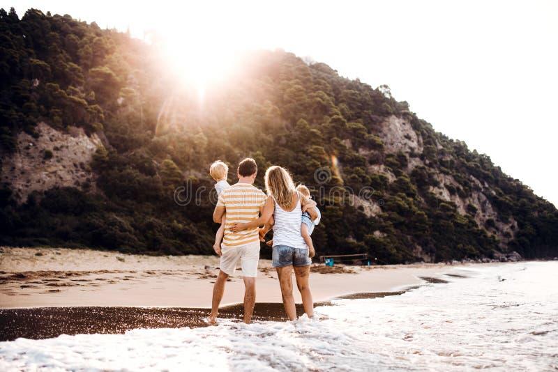 Una vista posterior de la familia con dos niños del niño que se colocan en la playa en la puesta del sol imagen de archivo libre de regalías
