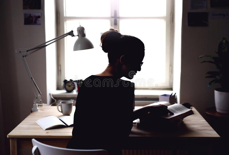 Una vista posterior del estudiante joven que se sienta en la tabla, estudiando fotografía de archivo