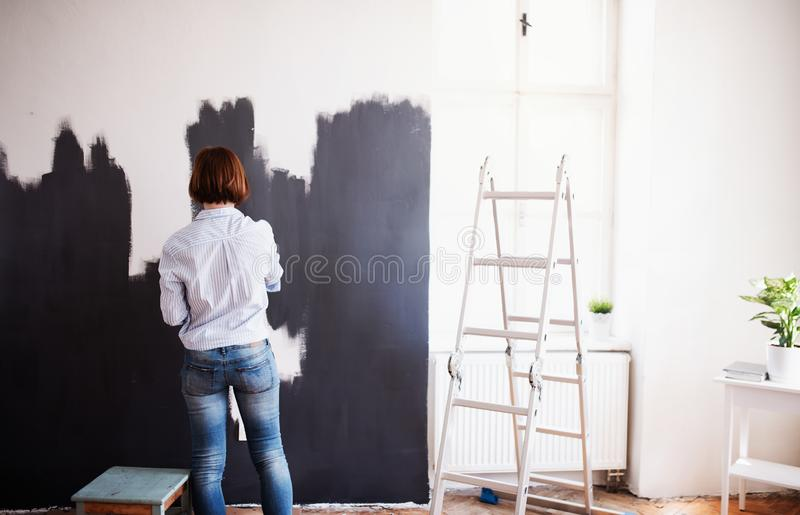 Una vista posterior del negro de la pared de la pintura de la mujer joven Un inicio de la peque?a empresa foto de archivo