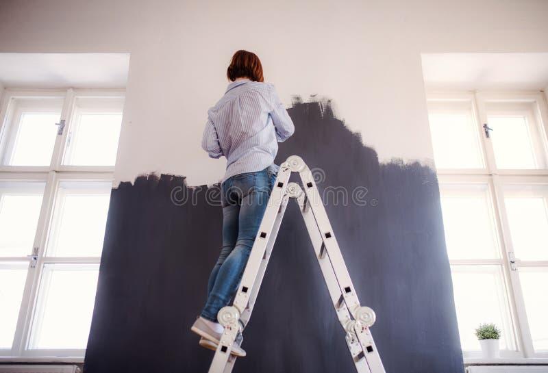 Una vista posterior del negro de la pared de la pintura de la mujer joven Un inicio de la peque?a empresa imagenes de archivo