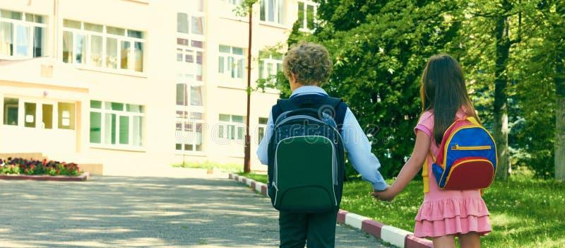 Una vista posteriore di due allievi della scuola primaria va di pari passo Ragazzo e ragazza con le borse di scuola dietro la par fotografie stock libere da diritti