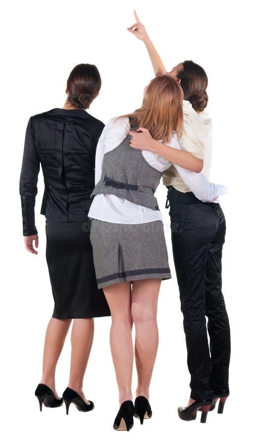 Una vista posteriore di indicare della donna di affari dei tre giovani. immagine stock libera da diritti