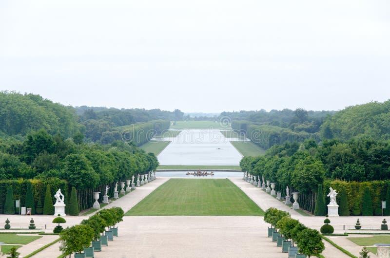 Una vista sola del parco di Versailles, Francia La combinazione geometrica di alberi verdi, di aree dell'erba e di statue bianche fotografia stock