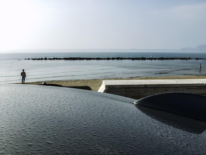 Una vista sul mare dalla cima del ` s dell'automobile, coperta di gocce di pioggia fotografia stock