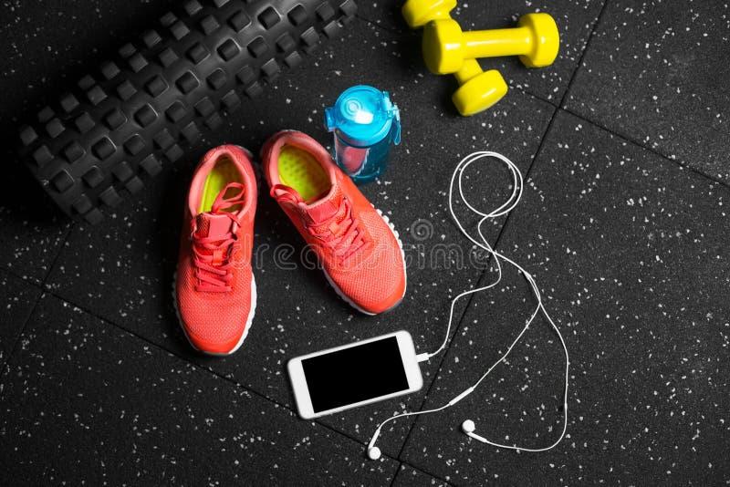 Una vista superior de instructores rosados, de la botella para el agua, del teléfono y de pequeños dumbells en un fondo negro Se  fotos de archivo