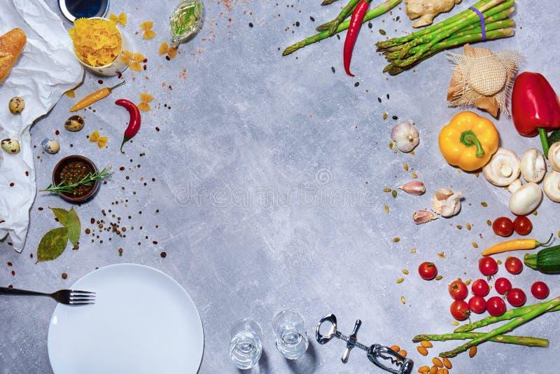 Una vista superior de una composición brillante de la cena en un fondo gris Vajilla al lado de una variedad de verduras coloridas fotos de archivo libres de regalías