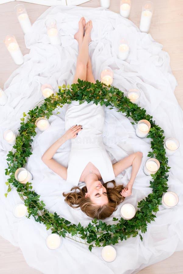 Una vista superior en una muchacha que miente en una guirnalda verde enorme rodeada quemando las velas, sonriendo amistoso Ella e foto de archivo libre de regalías
