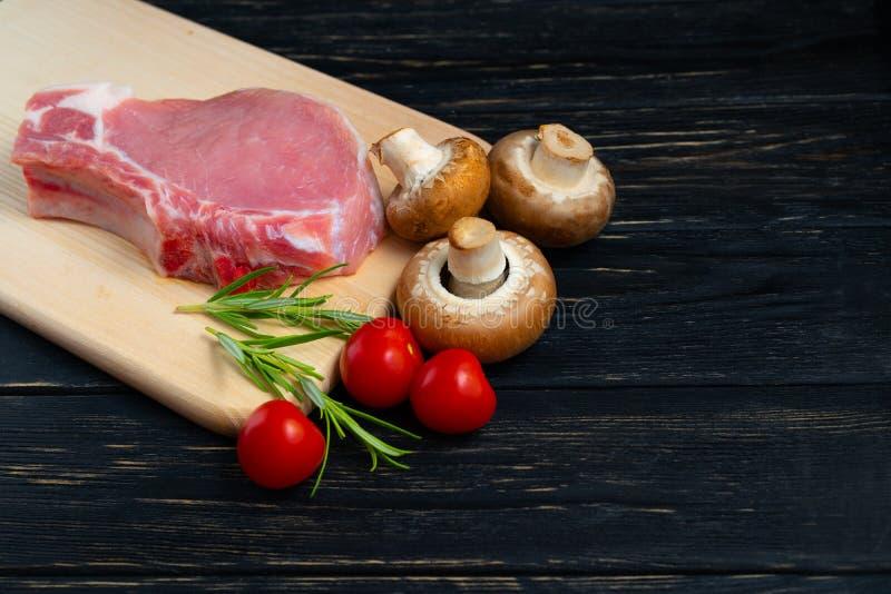 Una vista superiore di una collega le bistecche crude di braciola di maiale con i funghi e l'aglio del fungo prataiolo dei rosmar fotografia stock libera da diritti