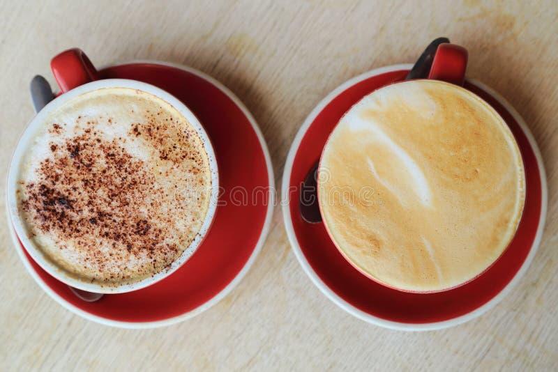 Una vista superiore di due tazze di caffè, di un latte e di una moca in tazza rossa su fondo di legno immagini stock